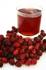 glass with red drink surrounded by a pile of cranberries