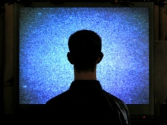 back of kid's head as he faces a large snowy television screen taking up the whole photo