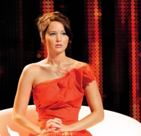 Katniss Everdeen, character of The Hunger Games played by Jennifer Lawrence, sits very stiffly with great posture in a big white chair on a stage in a form-fitting red dress
