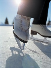 close up of a person's feet in white figure skates on the ice with a setting sun behind